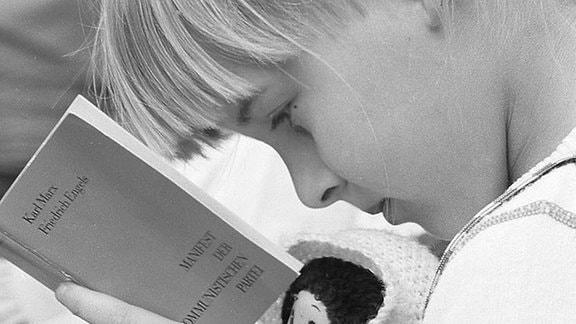 Ein junges Mädchen liest ein Buch.