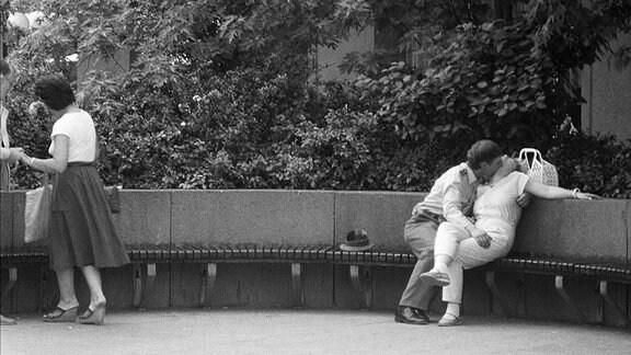 Ein Pärchen küsst sich auf einer Parkbank.