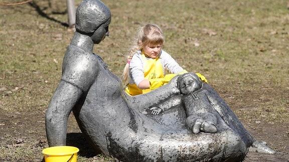 Mädchen putzt eine Statue