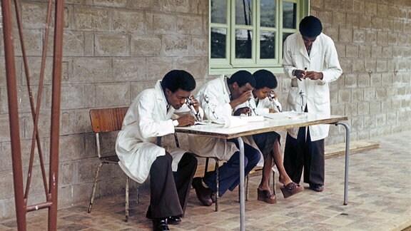Vier Ärzte sitzen im Freien an einem Tisch mit Mikroskopen.