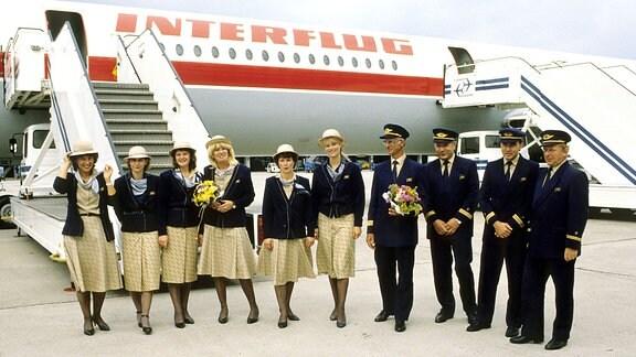 Gruppe Stewardessen vor dem Flugzeug
