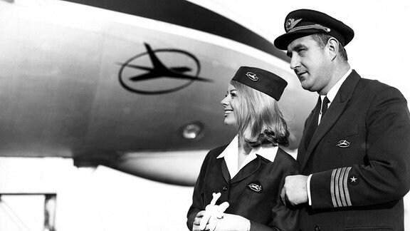 Pilot und Stewardess vor einem Flugzeug