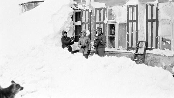 Drei Menschen stehen vor einem zugeschneiten Haus.