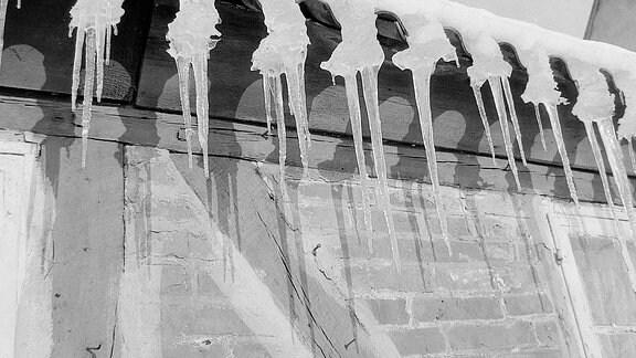 Eiszapfen hängen an einer Dachrinne.