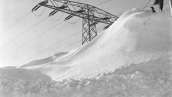 Fast vom Schnee verwehter Hochspannungsmast auf Rügen 1978/79