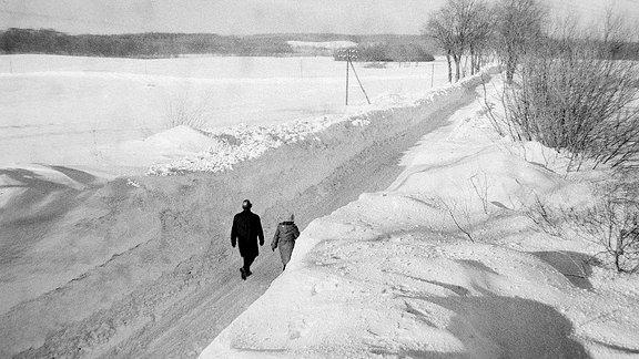 Zwei Menschen laufen zwischen hohen Schneewänden eine Straße entlang.