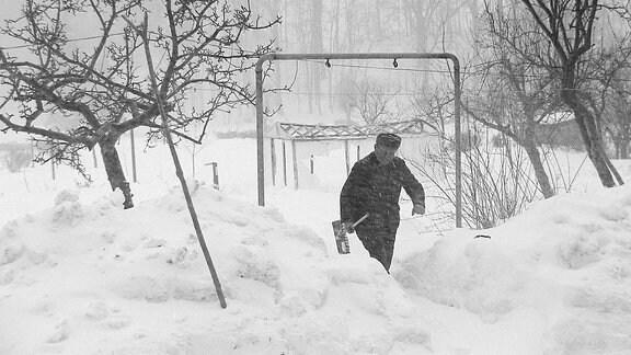 Ein Mann schippt Schnee.