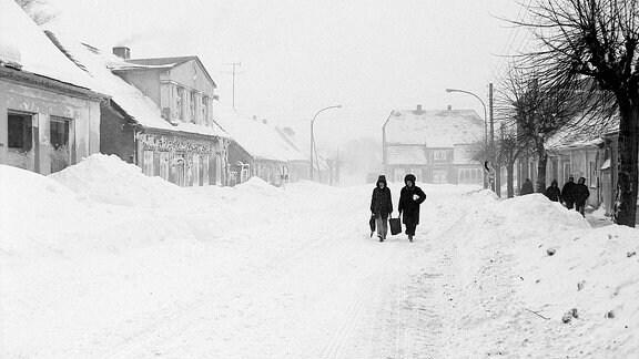 Zwei Menschen laufen durch eine schneebedeckte Straße.