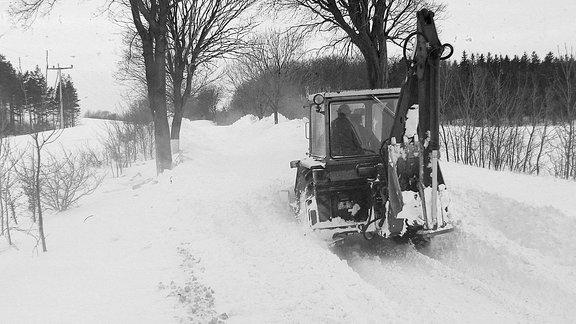 Ein Bagger fährt über eine mit Schnee bedeckte Straße.