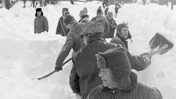 Eine Gruppe von Menschen beim Schneeschippen.