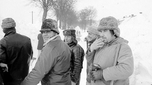 Menschen stehen mit Schaufeln im Schnee und rauchen.