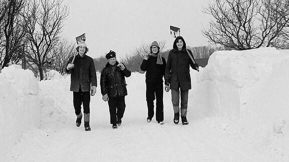 Vier Menschen mit Schaufeln in der Hand laufen durch Schnee.