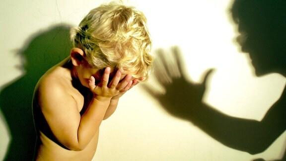 Ein kleines Kind hält die Hände vor das Gesicht, daneben der Schatten eines Mannes mit erhobener Hand.