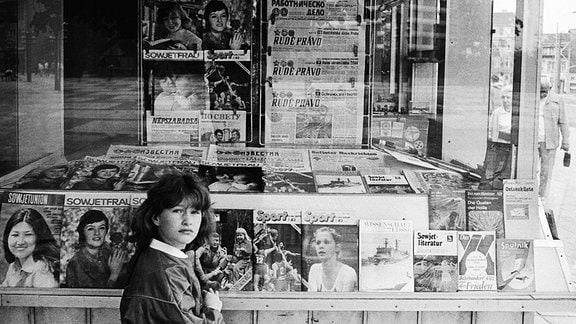 Mädchen vor einem Kiosk des Post-Zeitungs Vertriebes PZV der DDR in der Dunkerstrasse, das Sortiment besteht aus Zeitungen und Zeitschriften der DDR