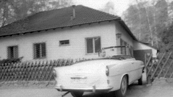 Köfer sitzt im Auto vor dem eigenen Wohnhaus.