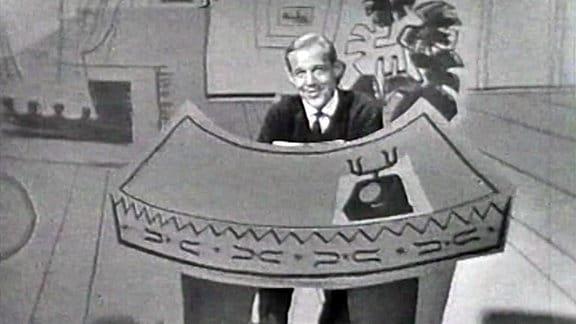 Herbert Köfer steht während Dreharbeiten für die Aktuelle Kamera hinter einer Papiercollage.