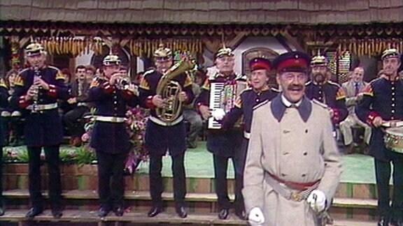 Köfer und Kapelle in Uniformen auf der Bühne