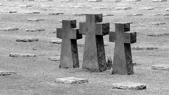 Drei Steinkreuze und Grabplatten auf einem Soldatenfriedhof