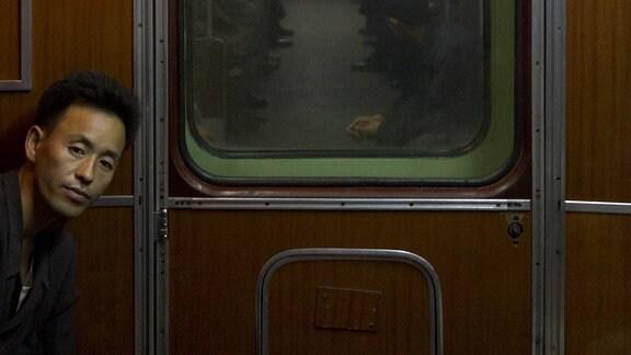 In einem Abteil, an dessen Wand Portraits von Kim Jong-il und Kim Il Sung hängen, schaut ein Passagier 2011 in die Kamera.