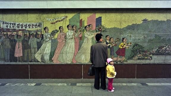 Ein kleiner Junge an der Hand seines Vaters vor einem Wandgemälde 2000 in Pjöngjang