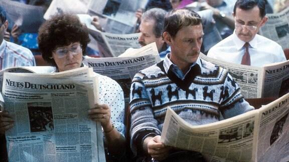 Delegierte anlässlich des Sonderparteitages der SED 1989 bei der Lektüre des Parteiorgans - Neues Deutschland - in Berlin, 1989