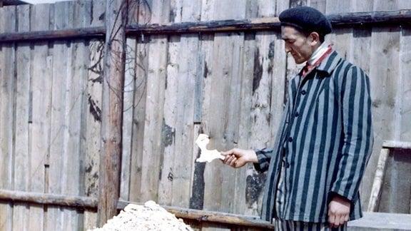 Krematorium Buchenwald, ehem. Häftling 1945 vor einem Berg eingeäscherter Mitgefangener