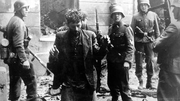 Zwei jüdische Männer, die sich in einem Haus versteckt hatten, werden von SS-Soldaten gefangen genommen