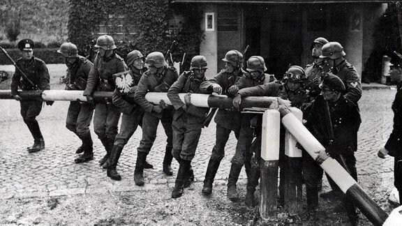 Deutsche Soldaten durchbrechen 1939 einen Schlagbaum an der Grenze zu Polen.