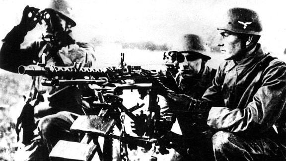 Drei Fallschirmjäger an einem Maschinengewehr MG 34