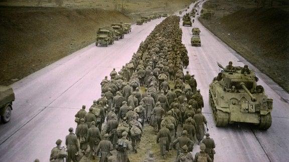 Gefangene deutsche Soldaten und US-Truppen 1945 auf einer Autobahn