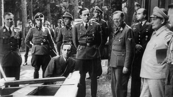 Joseph Goebbels, Hermann Göring und Hitlers Adjudant Schaub betrachten nach dem misslungenen Attentat 1944 zerstörte Möbelstücke.