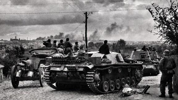 Deutsche Soldaten mit Panzerfahrzeugen beobachten Luftangriff auf Stadt in Frankreich 1940