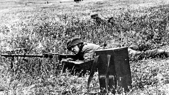 Deutscher MG-Schütze liegt auf einem Feld, während der Wehrmachtsínvasion auf Kreta.