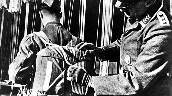 Der Fallschirm eines deutschen Fallschirmsoldat wird kontrolliert.