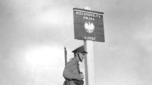 Ein polnischer Soldat steht 1939 neben einem Grenzschild auf dem Magyan Pass.