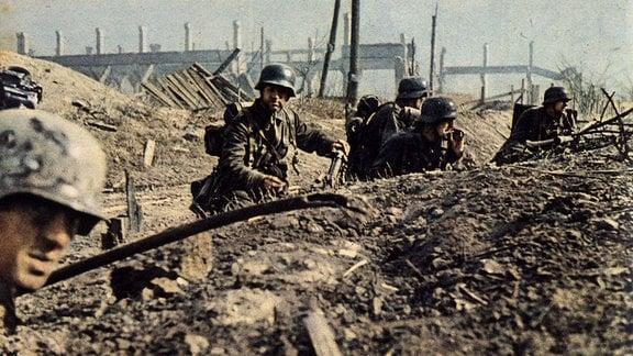 Wehrmacht-Soldaten kauern im Graben eines Schlachtfeldes.