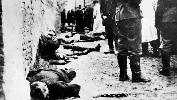 Szene nach der Erschießung von Serben, zeigt Wehrmachtssoldaten im Vordergrund.