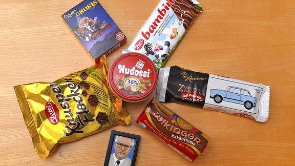 Verschiedene Süßigkeiten liegen auf einem Tisch neben einem Bild von Erich Honecker