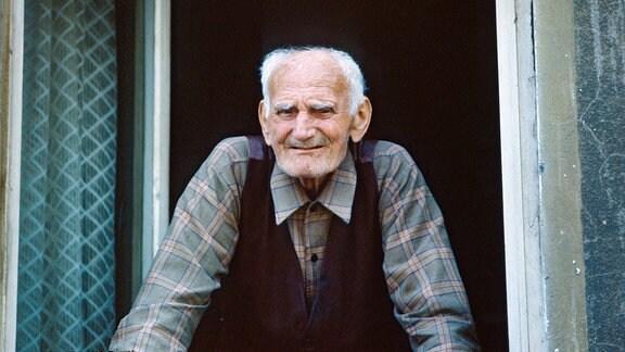 Alter Mann schaut laechelnd aus einem Fenster.