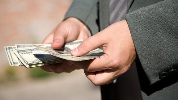 Mann mit Geldscheinen in den Händen