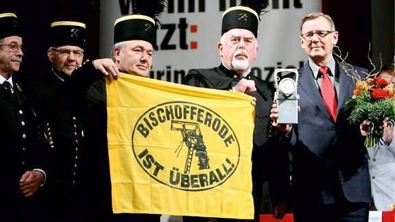 Thüringens Ministerpräsident mit und andere Männer halten eine Bischofferode-Flagge.