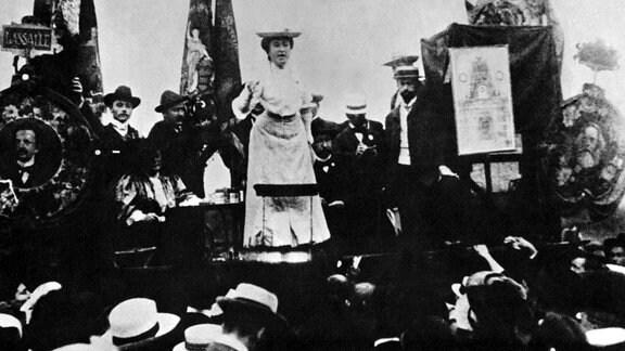 Rosa Luxemburg spricht und Klara Zetkin sitzt mit den Portraits von Marx und Lassalle bei einem sozialistischen Treffen in Stuttgart. 1900