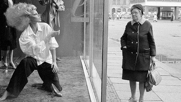 Eine Frau schaut in ein Schaufenster für Mode, in der DDR.