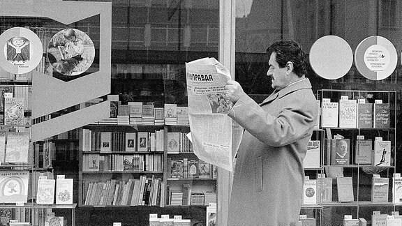 Ein Mann liest eine Zweitung vor einem Schaufenster.