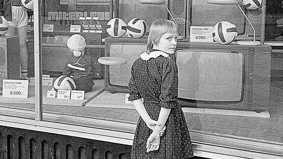 Ein Mädchen steht vor einem Schaufenster in der DDR.
