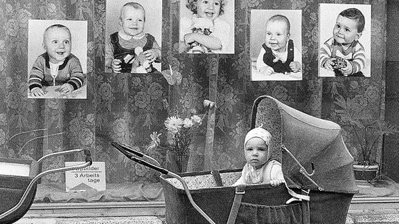 Ein Kinderwagen mit Baby, steht vor einem Schaufenster in der DDR.