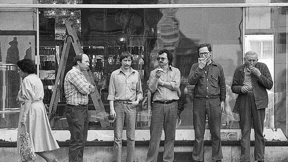Männer stehen vor einem Schaufenster eines Lampenladens, in der DDR.