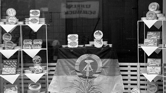 Blick in ein Schaufenster mit Konserven, in der DDR.