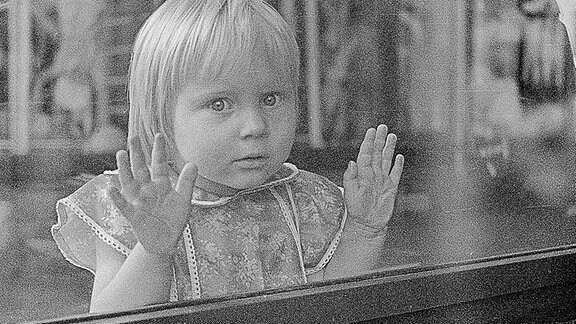 Ein Mädchen schaut durch ein Schaufenster in der DDR.