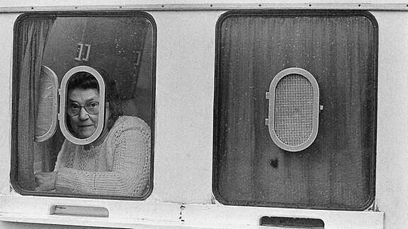 Eine Frau schaut aus einem Fenster für LVB-Sammelkarten.